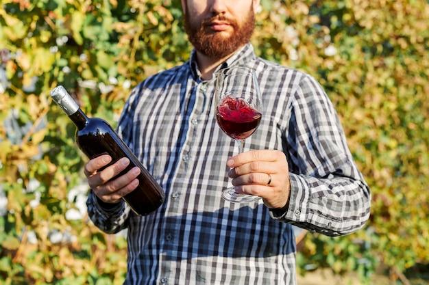 Ritratto di bel produttore di vino che tiene in mano una bottiglia e un bicchiere di vino rosso e assaggiandolo, controllando la qualità del vino mentre si trova nei vigneti.