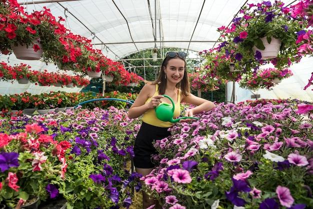 Ritratto di donna bella giardiniere innaffiare piante e fiori in serra