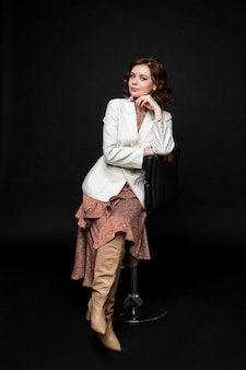 Ritratto di una bella donna in abito lungo e stivali si siede su una sedia e posa per la telecamera, immagine isolata su sfondo nero