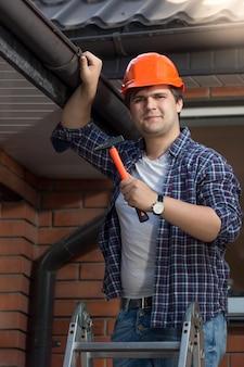 Ritratto di bel lavoratore in elmetto protettivo in posa con martello su scala a pioli