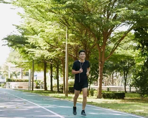 Ritratto di uno sportivo giovane ragazzo asiatico bello fare jogging ascoltando musica di formazione