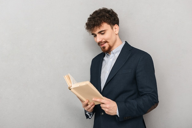 Ritratto di un bel giovane uomo d'affari isolato su un libro di lettura muro grigio.
