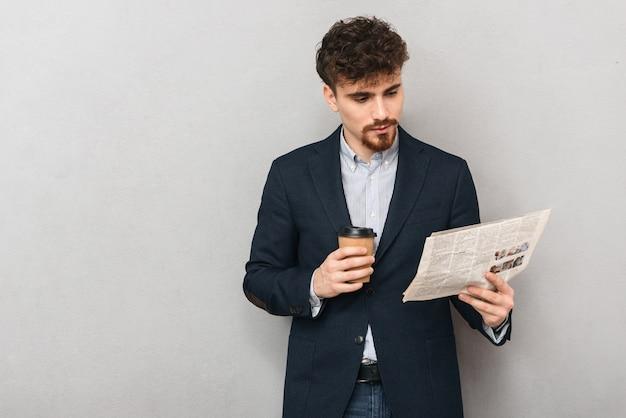 Ritratto di un bel giovane uomo d'affari isolato su muro grigio leggendo il giornale di bere il caffè.
