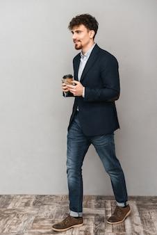 Ritratto di un bel giovane uomo d'affari isolato su muro grigio utilizzando il telefono cellulare bere caffè.