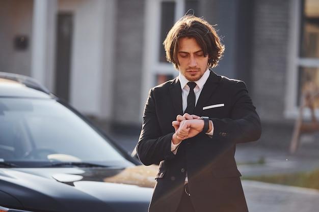 Ritratto di bel giovane uomo d'affari in abito nero e cravatta all'aperto vicino a un'auto moderna in città.
