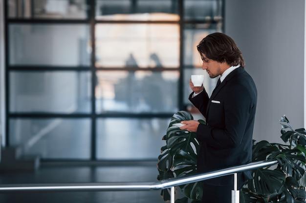 Ritratto di bel giovane uomo d'affari in abito nero e cravatta si trova al chiuso con una tazza di bevanda.