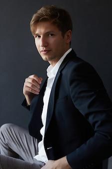 Ritratto di un bel giovane uomo d'affari in abito elegante, su sfondo nero.