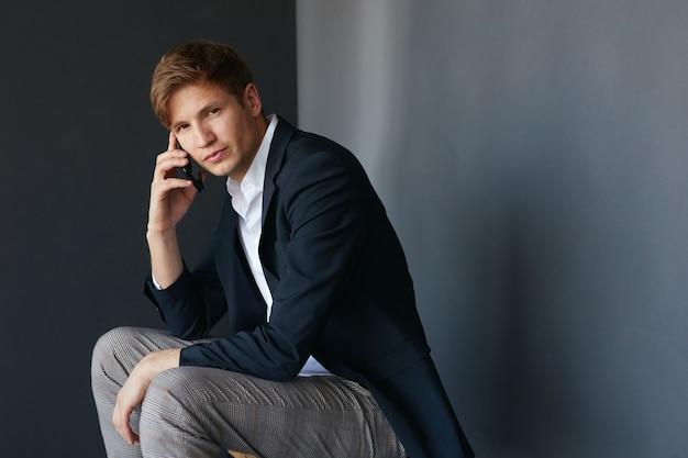 Ritratto di un bel giovane uomo d'affari in abito elegante seduto e guardando la fotocamera, tenendo il telefono vicino all'orecchio, su sfondo nero.