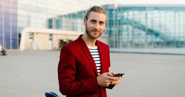 Ritratto di bel giovane uomo caucasico in giacca rossa in piedi all'aperto con la bici, mandare sms su smartphone e sorridere alla telecamera. maschio felice attraente toccando e scorrendo sul telefono cellulare.