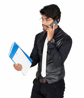 Ritratto di un bel giovane in chat sul telefono cellulare, isolato su bianco