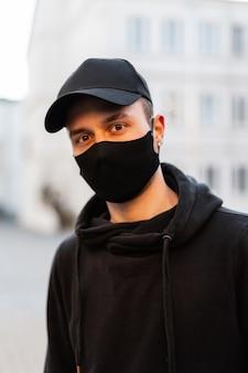 Ritratto di un bel giovane modello hipster con maschera medica protettiva e berretto mockup nero alla moda che indossa una felpa con cappuccio alla moda in città
