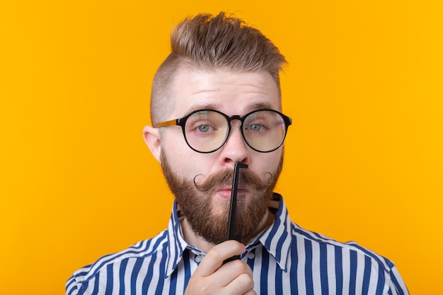 Ritratto di un bel giovane maschio hipster con baffi e barba che pettina i baffi su una parete gialla