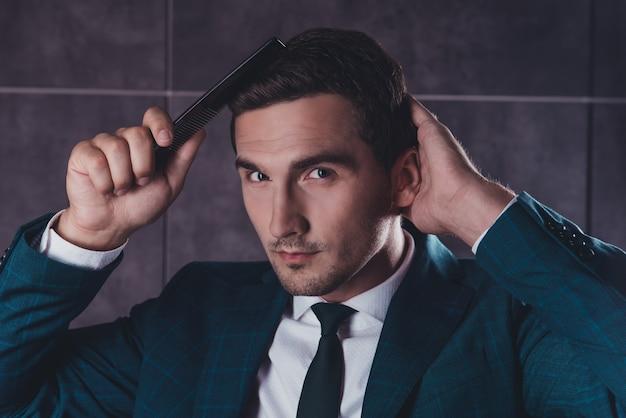 Ritratto di un bel giovane in abito nero, pettinare i capelli