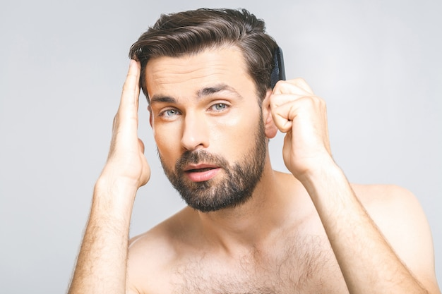 Ritratto del giovane bello che pettina i suoi capelli in bagno. isolato su sfondo grigio.