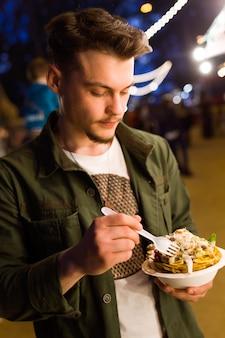 Ritratto di bel giovane che mangia patatine in strada.