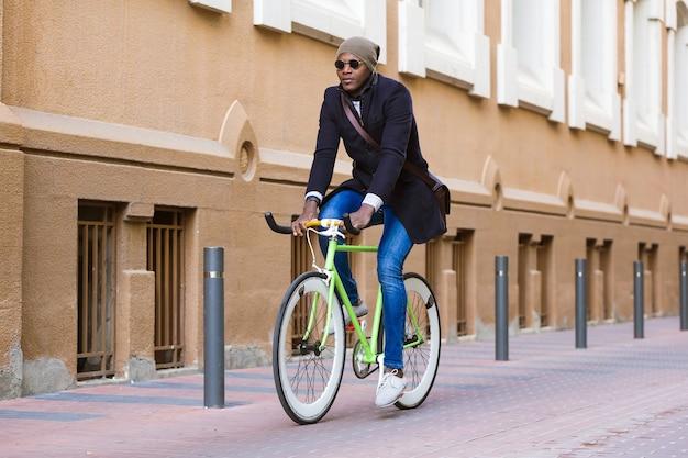 Ritratto di bel giovane in sella a una bicicletta in strada.