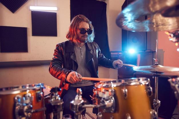 Ritratto di bel giovane a dondolo tamburi durante il concerto di musica o le prove in studio