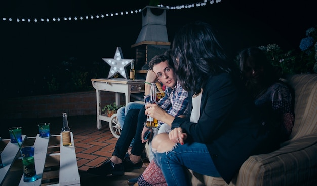 Ritratto di bel giovane seduto e parlare con un'amica che tiene la birra in una festa all'aperto. concetto di amicizia e celebrazioni.