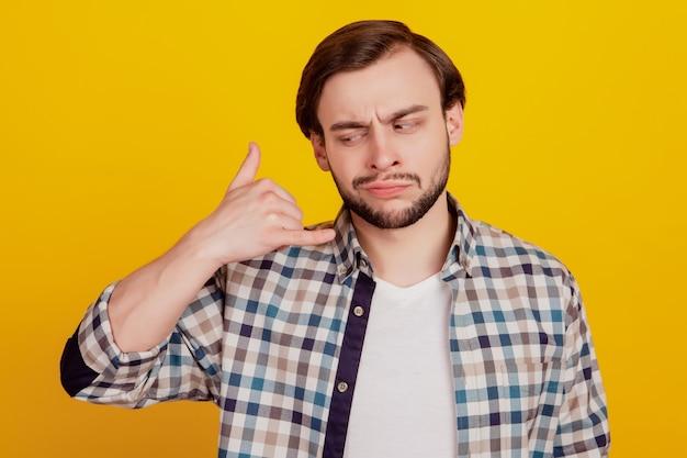 Ritratto di un bel giovane infelice triste sconvolto negativo mostra segno telefonico chiamata dito isolato su sfondo di colore giallo