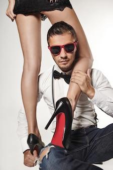 Ritratto di un bel giovane con occhiali da sole alla moda con gambe da ragazza sul muro