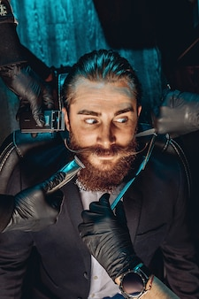 Ritratto di un bel giovane con baffi e barba in un negozio di barbiere e guardando con sorpresa.