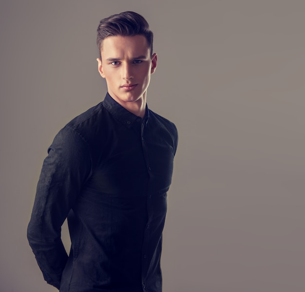 Ritratto di un bel giovane con acconciatura alla moda, vestito con una camicia nera abbottonata alla moda.