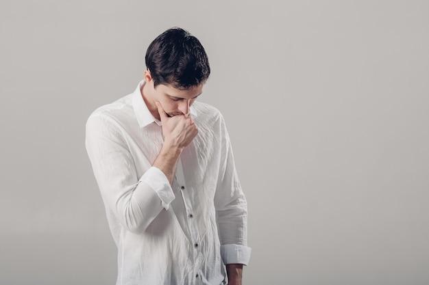 Ritratto di giovane uomo castana pensieroso bello in camicia bianca su fondo grigio. luce soffusa