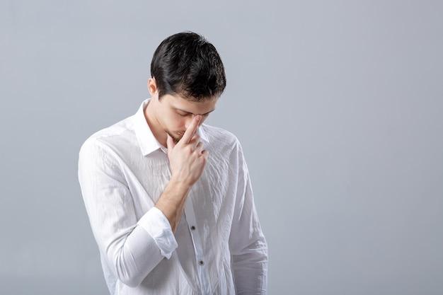 Ritratto di giovane uomo castana pensieroso bello in camicia bianca su fondo grigio.