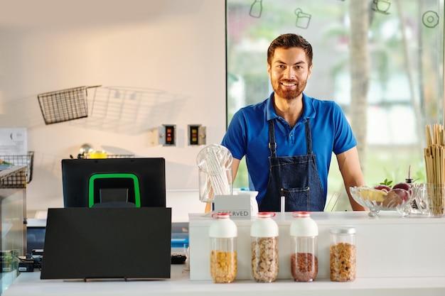 Ritratto di un bel giovane lavoratore di caffè sorridente in piedi al bancone in attesa dei clienti