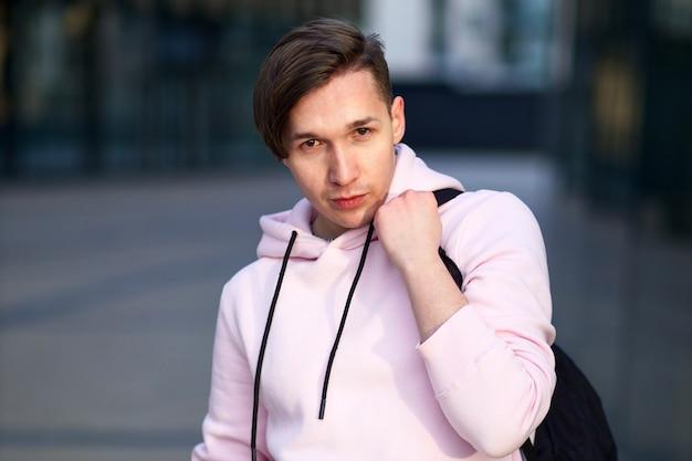 Ritratto di un bel giovane studente universitario o di college in felpa con cappuccio rosa con zaino all'aperto