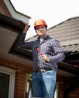Ritratto di tuttofare in piedi su una scala alta e ispezione del tetto della casa