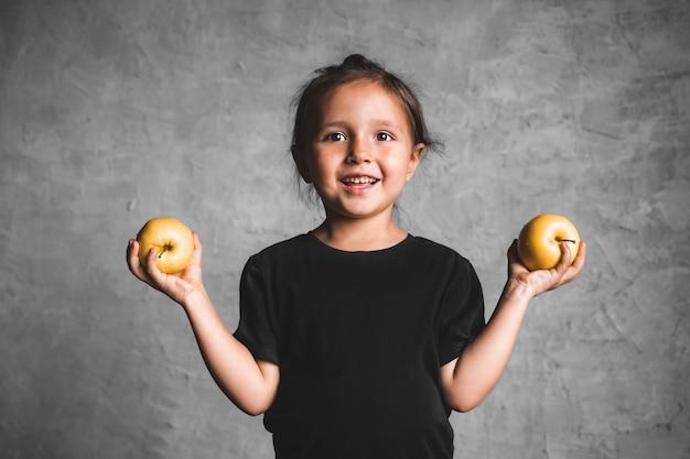 Ritratto di una bambina di felicità che mangia una mela verde su sfondo grigio. salute, cibo sano