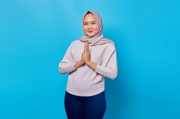 Ritratto di felicità giovane donna asiatica che tiene la mano su supplica su sfondo blu