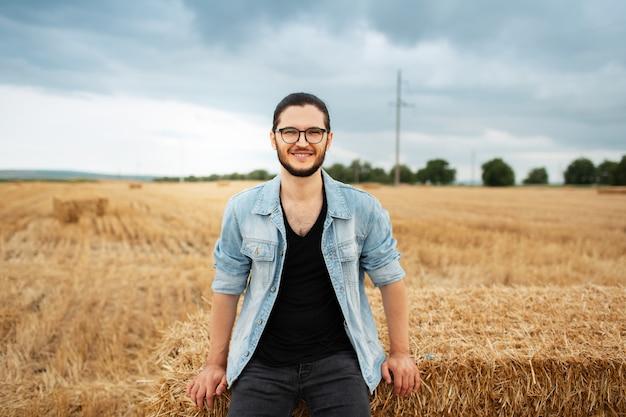 Ritratto di giovane ragazzo di felicità in piedi vicino a mucchi di fieno nel campo di grano.