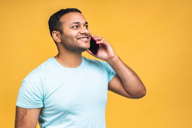 Ritratto di un uomo indiano nero afroamericano felice che parla sul telefono cellulare isolato sopra fondo giallo.