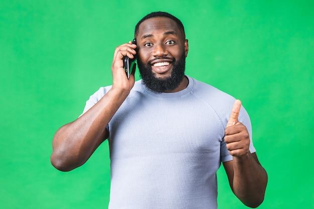 Ritratto di un uomo di colore afroamericano felice che parla sul telefono cellulare isolato sopra fondo verde. pollice su.