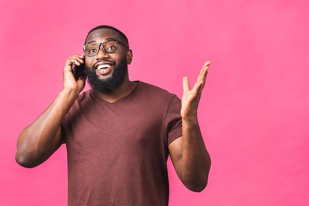 Ritratto di un uomo di colore afroamericano felice che parla sul telefono cellulare isolato sopra fondo rosa.