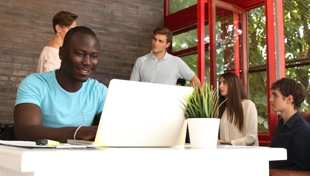 Ritratto di un felice imprenditore afroamericano che mostra il computer in ufficio