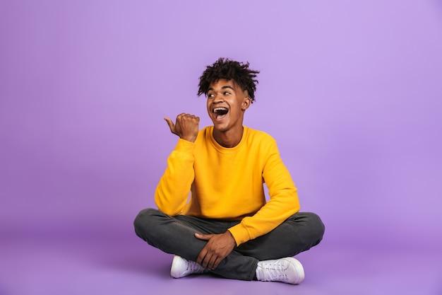 Ritratto di felice ragazzo afroamericano sorridente e puntando il dito da parte a copyspace, mentre è seduto sul pavimento con le gambe incrociate, isolato su sfondo viola