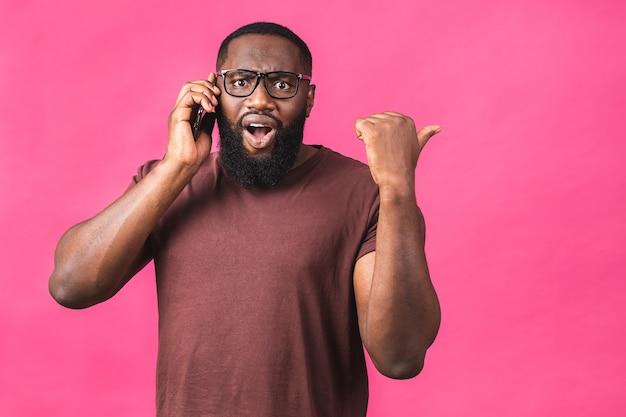 Ritratto di un ragazzo afroamericano felice che parla al telefono cellulare isolato su sfondo rosa. dito puntato.