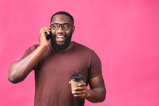 Ritratto di un ragazzo afroamericano felice che parla al telefono cellulare isolato su sfondo rosa.