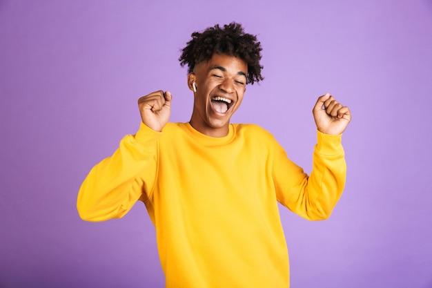 Ritratto di uomo africano felice che ha un'elegante pettinatura afro ballando e cantando, mentre si ascolta musica tramite auricolare bluetooth, isolato su sfondo viola