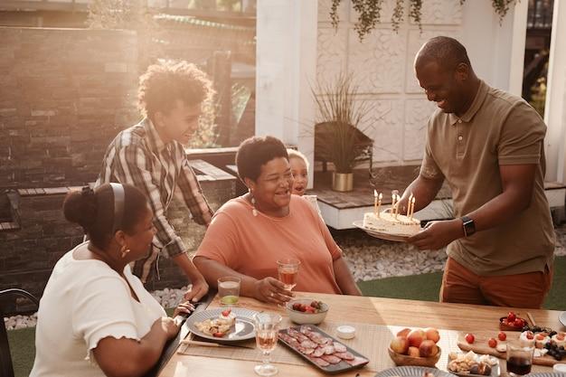 Ritratto di famiglia afroamericana felice che festeggia il compleanno della nonna all'aperto illuminato dalla luce del sole...
