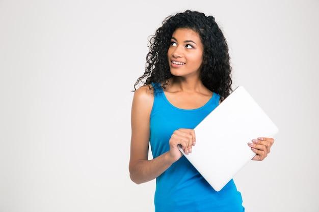 Ritratto di un computer portatile afroamericano felice della tenuta e distogliere lo sguardo sul copyspace isolato su una parete bianca
