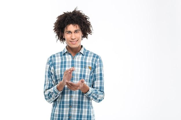 Ritratto di un uomo afroamericano felice che batte le mani isolato su un muro bianco