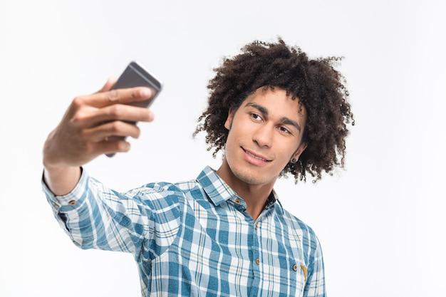 Ritratto di un uomo afroamericano felice che fa la foto del selfie sullo smartphone isolato su una parete bianca
