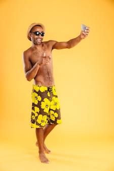 Ritratto di un uomo afro felice in costume da bagno che fa la foto del selfie sullo smartphone isolato su una parete arancione