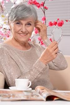 Ritratto di una donna anziana felice che beve caffè