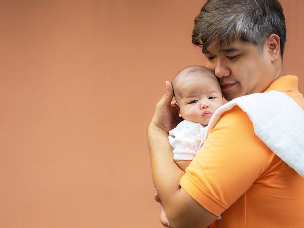 Il ritratto del padre felice dell'asia che tiene il suo neonato dolce neonato si è vestito in vestiti bianchi.