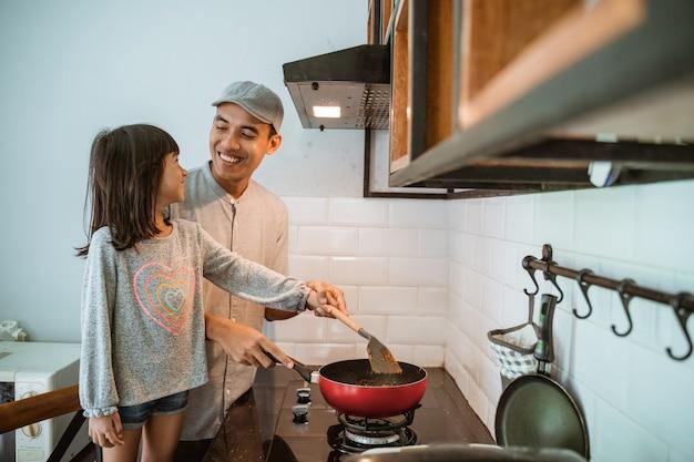 Ritratto del padre e della figlia asiatici felici che cucinano insieme nella cucina moderna